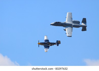 ROCHESTER - JULY 17: A WWII era P-51 Mustang fighter airplane and a current-model A-10 Thunderbolt ground attack airplane flying in formation at an airshow in Rochester, NY on July 17, 2011.