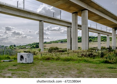 ROCHESTER, KENT, UK - CIRCA JULY 2017: Illegally discarded washing machine seen abounded under a major motorway crossing, spanning the River Medway in Kent, showing its superstructure.