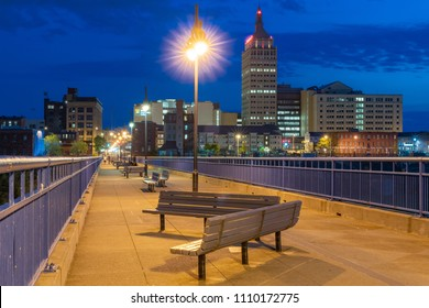 ROCHESTER, NY - MAY 14, 2018: Skyline of Rochester, New York along the Pont De Rennes Pedestrian Bridge which is part of the Genesee Riverway Trail at night