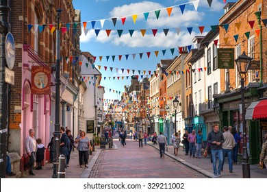 ROCHESTER, UK - MAY 16, 2015: Rochester high street at weekend. People walking through the street, passing cafes, restaurants and shops