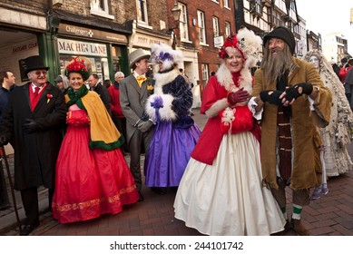 ROCHESTER, UK-DECEMBER 6: Couples dressed in fine Victorian costumes parade in the streets in the annual Rochester Dickensian Christmas Festival,   December 6, 2014, Rochester UK.
