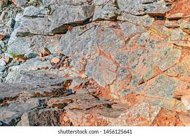 Rock background with dry earth in the cracks between the stones. Flagstone.