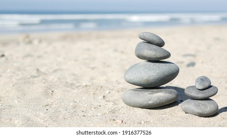 Rock balancing on ocean beach, stones stacking by sea water waves. Pyramid of pebbles on sandy shore. Stable pile or heap in soft focus with bokeh, close up. Zen balance, minimalism, harmony and peace