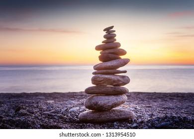 Rock balancing or stone balancin,  naturally balanced on a beach with the sea behind