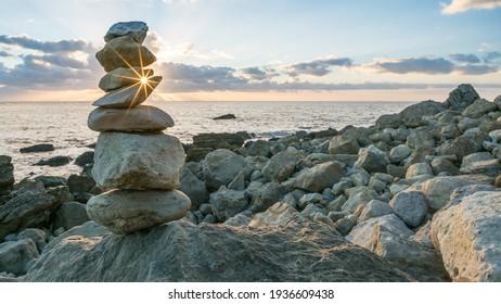 Rock Balancing at sundown at Rocken End, Isle of Wight, England