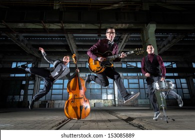 Rock band jumps into the air in an old industrial building