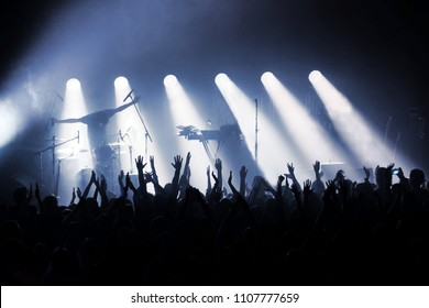 rock band on stage in rays of spotlights in front of crowd of fans with their hands up