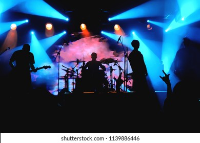 Rock band on a stage silhouettes in a colorful backlights