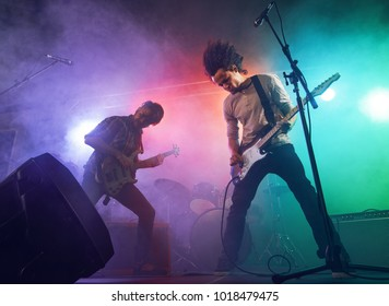 Rock band performs on stage. Guitarist, bass guitar and drums. The guitarist plays solo.