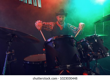 Rock band performs on stage. Guitarist, bass guitar and drums. Scene, light.