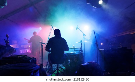 Rock band playing with smoke, seen from behind