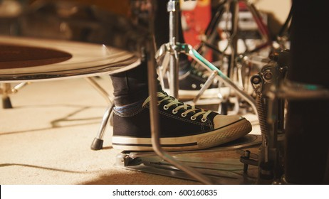 Rock band rehearsing in the garage - drummer's foot wears sneakers moving drum bass pedal