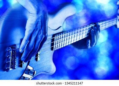 rock bassist hands playing electric bass guitar live on stage