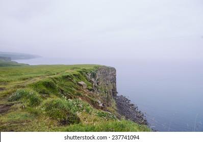 rock beach cliff edge on a foggy rainy weather, dark ocean