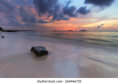 Rock and beach scene during sunset.