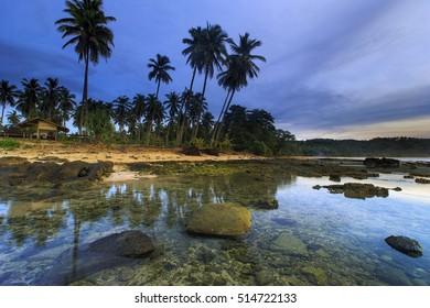 rock and blue sky before sunrise,,sawarna Beach banten indonesia