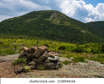 A rock cairn on an exposed mountain saddle in Maine, along the Appalachian Trail, with a view of a nearby mountain summit.
