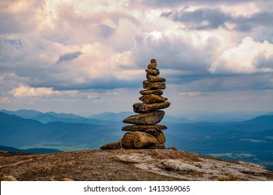 A Rock Cairn, Rocks Piled On Top Of Each Other, Marking A Hiking Trail, On The Summit Of Cascade Mountain In The Adirondack Mountains In New York State