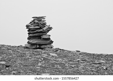 A rock cairn (rock stack) on top of a mountain with fog in the background. Finding your way concept image. Black and white image.
