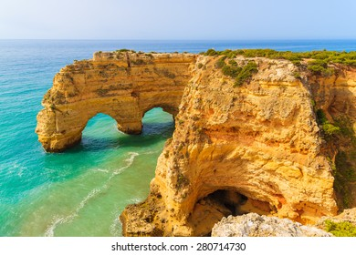 Rock cliff arches on Marinha beach and turquoise sea water on coast of Portugal in Algarve region