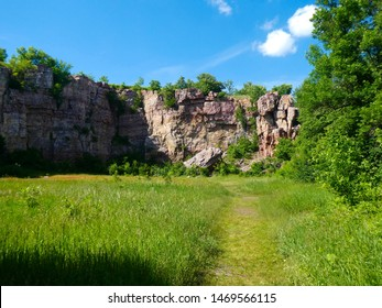 Rock cliff at an old quarry (Blue Mounds State Park) with a grassy field and blue sky in the summer.