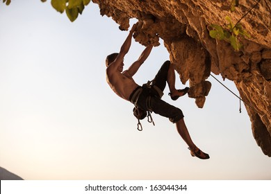 Rock climber against sky at sunset