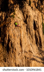 Rock climber ascending a challenging cliff