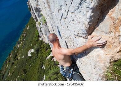 Rock climber climbing on the cliffs of Masua, west coast of Sardinia, Italy
