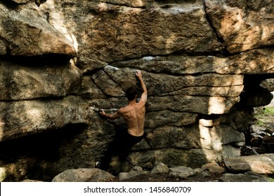Rock climber climbs bouldering on a cliff on forest. Low angle of strong rock climbing man hanging free on rock with sunflare