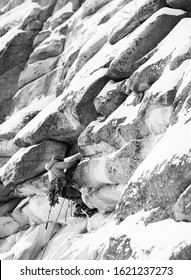 Rock climber climbs up a snowy rock wall during a winter ascent in the mountains, black and white vertical panorama.
