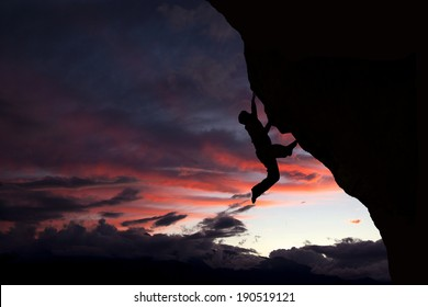 Rock climber clinging to overhang with a nice sunset background