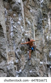 Rock climber clipping rope on a sport route in Squamish, British Columbia, Canada.