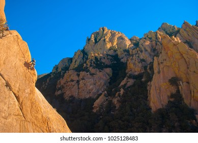 Rock climber in desert with beautiful view of rock formations in southern Arizona.