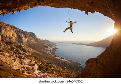 Rock climber hanging on rope while lead climbing at sunset