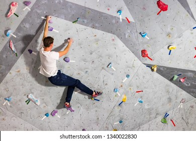 Rock climber man hanging on a bouldering climbing wall, inside on colored hooks