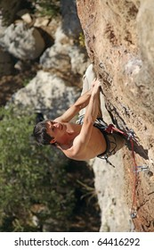 Rock climber on the cliff, vertical view