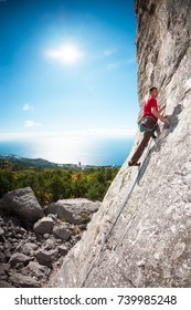 A rock climber on a rock. A man climbs the rock against the background of the sea coast. Active lifestyle. Sports in nature. Overcoming a difficult climbing route.