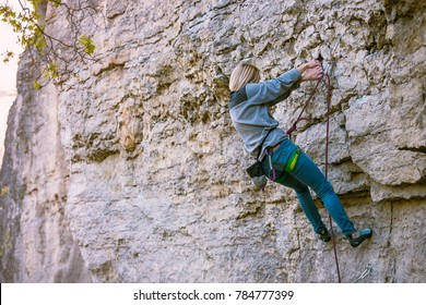A rock climber on a rock. A woman goes in for sports in nature. The strength and endurance of climbers. Climb to the top of the cliff.