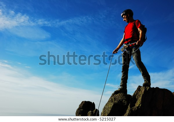 Rock climber, partial cloudy sky, horizontal orientation