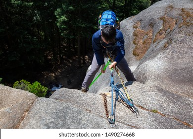Rock Climber is Rappeling down a steep cliff during a sunny summer day. Taken in Squamish, British Columbia, Canada.