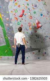 Rock climber stands and looks at the climbing wall with hooks in the boulder hall