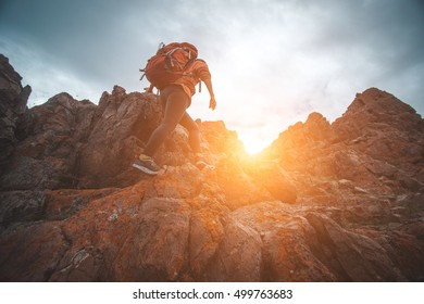 Rock climber young traveling woman climb to the summit.