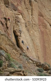 Rock climbers and belayers on sheer cliff,Smith Rock State Park, Central Oregon
