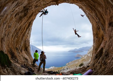 Rock climbers in cave: belayers watching leading climbers, two climbers swinging on ropes or being lowered down, one male gripping handhold on cliff and looking down