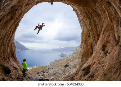Rock climbers in cave: leading climber flexing muscles jokingly, his partner belaying