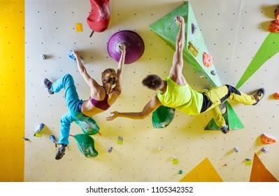 Rock climbers in climbing gym. Young couple climbing bouldering problems (routes), man encouraging girl climber.