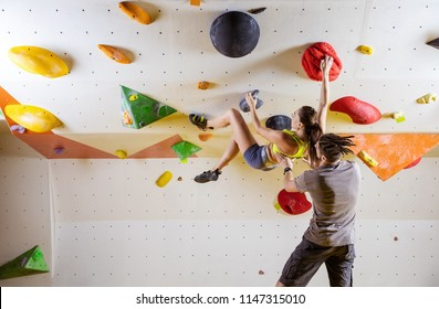 Rock climbers in climbing gym. Young woman climbing bouldering problem (route) on overhanging wall, male instructor securing her.