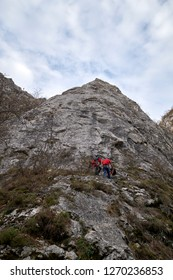 Rock climbers getting ready for alpinism activity going up the rope on top of the mountain