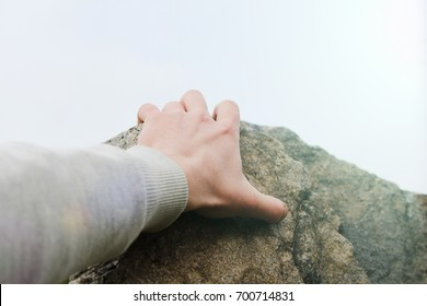 Rock climber's hand grasping handhold on cliff. Depth of field