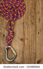 Rock climbing gear with rope and connector on rustic wooden background often used for belay or abseiling by mountaineers